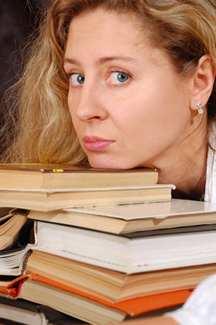 Woman resting chin on stack of books