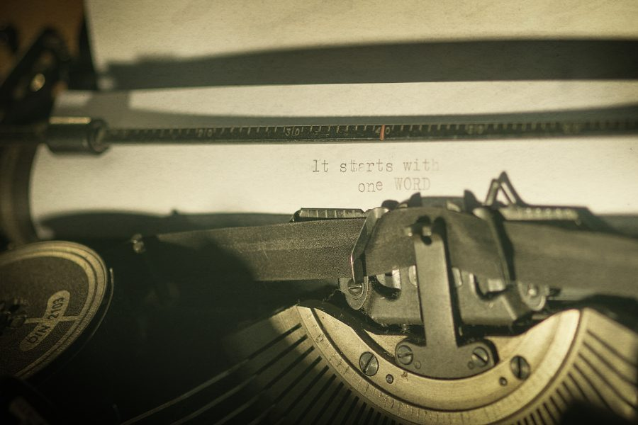 "A vintage typewriter with the text ""it starts with one WORD"" written on a shee"