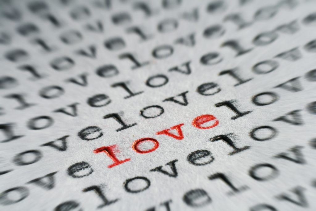 Typewritten page repeating LOVE with one word highlighted in red